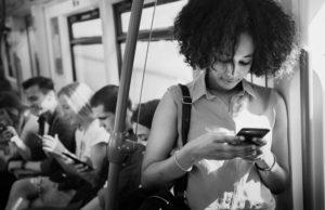 Uma jovem mulher negra está em um transporte público usando o celular.